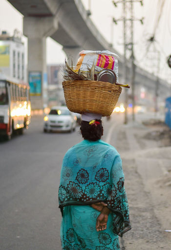Rear view of woman carrying basket on head