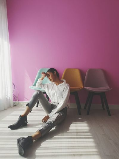 Full Length Of Depressed Woman Sitting On Floor At Home