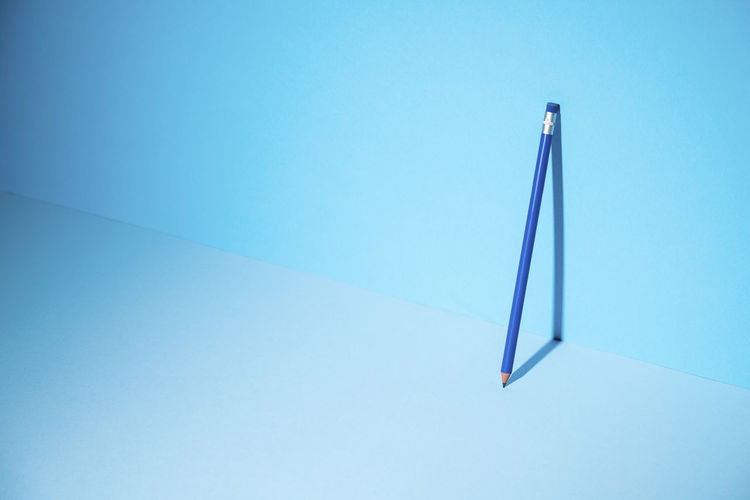 Low angle view of colored pencils against blue sky