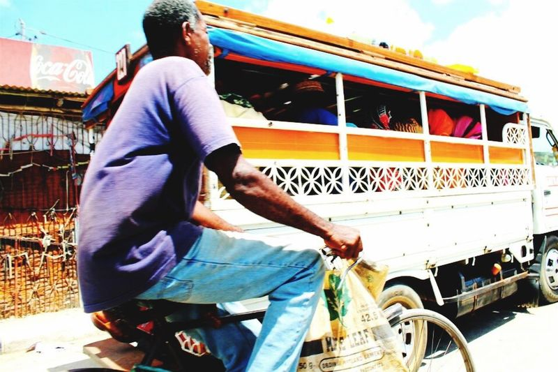 Street view Zanzibar Local Market Local People Colourful Man On Bike Local Bus Driving By
