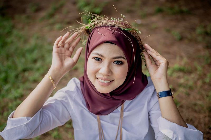 Portrait of smiling young woman in hijab wearing wreath on field