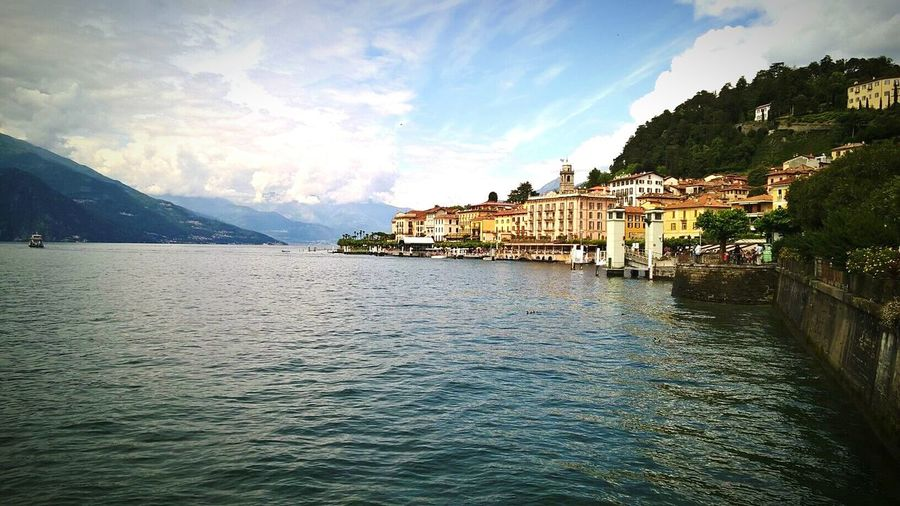 Residential district by lake como against cloudy sky