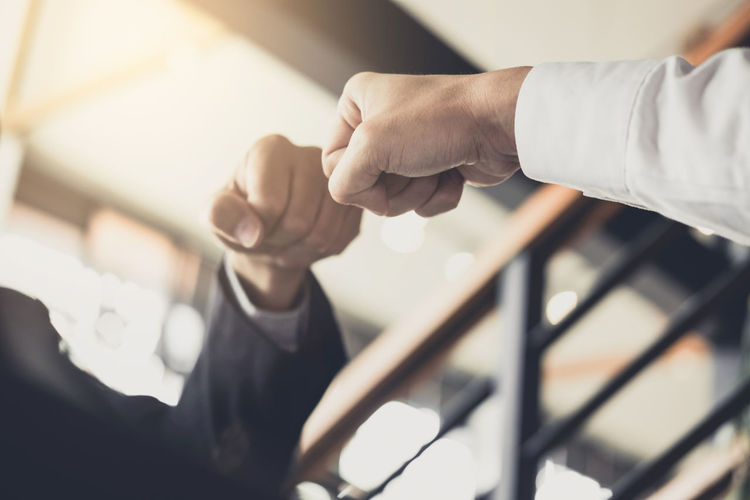 Cropped image of business people giving fist bump in office