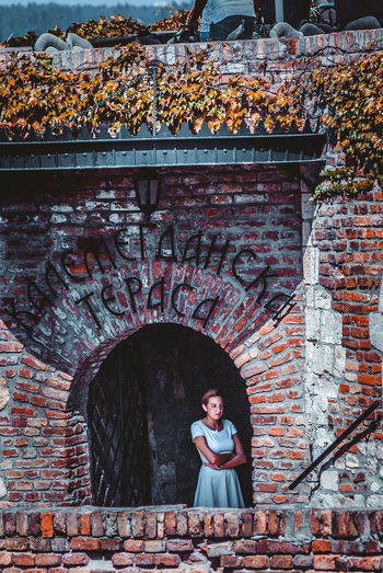 Woman looking away while standing by brick wall