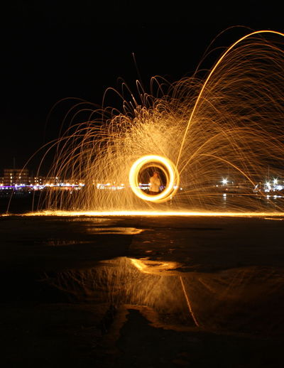 Man Spinning Wire Wool Against Sky At Night