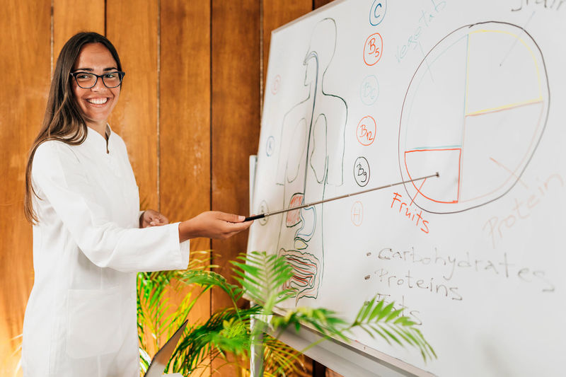 Female nutritionist standing in front of the white board smiling and explaining meal plan