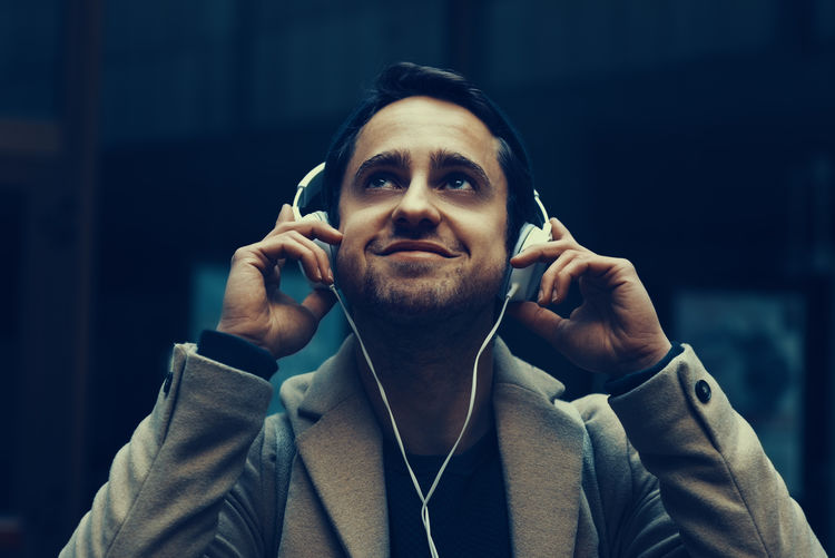 Close-Up Of Young Man Wearing Headphones Against Building