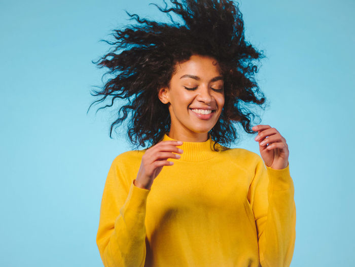 Happy Young Woman With Tousled Hair Against Blue Background