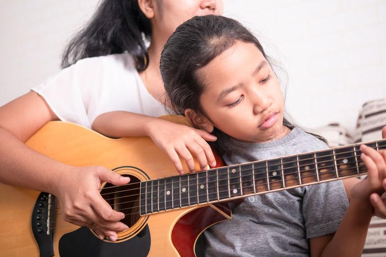 Mother teaching daughter to guitar