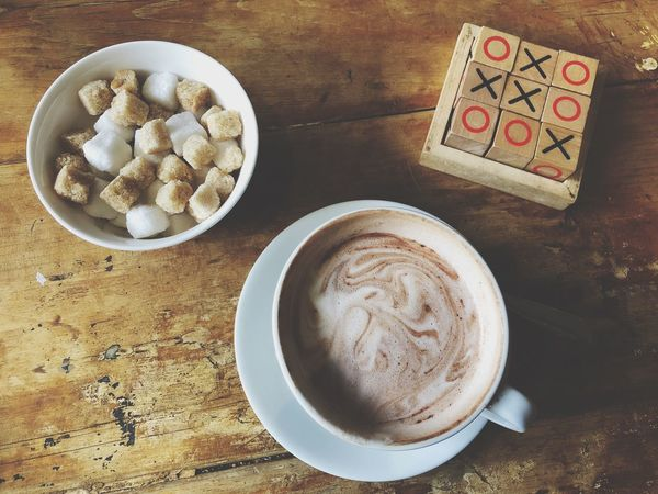 Hot chocolate and games Game Break Noughts And Crosses Tic Tac Toe Sugar Wood Table Hot Chocolate Latte Coffee Frothy Drink Directly Above Food Drink Freshness Day Cappuccino Close-up Ready-to-eat Froth Art
