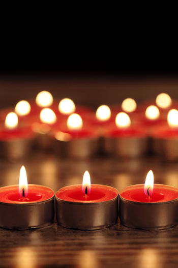 Close-up of lit candles in row