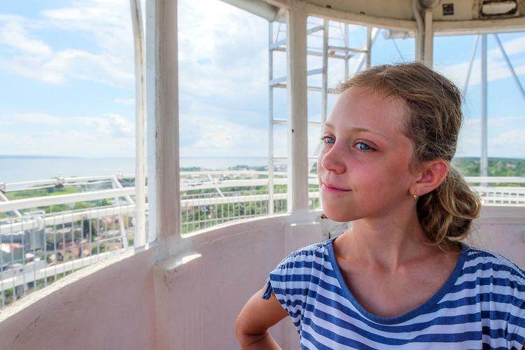 Girl looking away by window