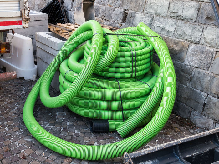 Roll of plastic pipe for road works. Protection of electric or telephone cables Green Color Day No People Pipe - Tube Connection Plastic Outdoors Hose Close-up Technology Container Cable High Angle View Wall Wall - Building Feature Equipment Nature Inflatable  Safety Garden Hose Roadwork Construction Industry