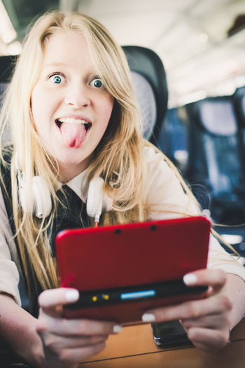 Portrait of cheerful teenage girl sticking out tongue while using mobile phone in train