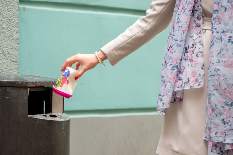 Midsection of woman throwing disposable cup in garbage bin
