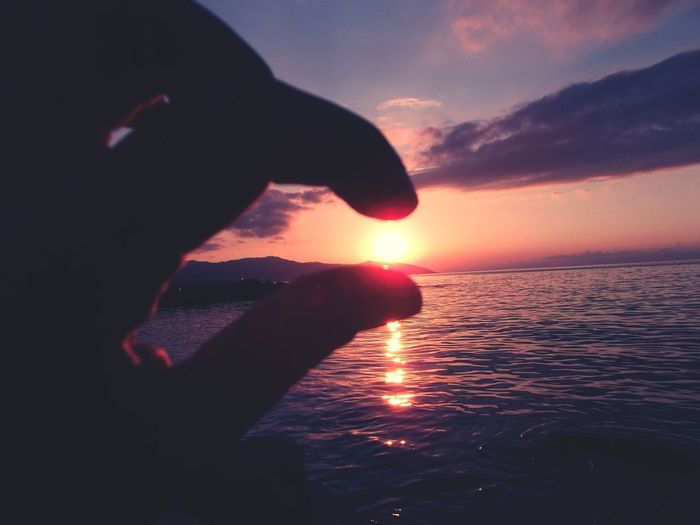 Silhouette hand against sea during sunset