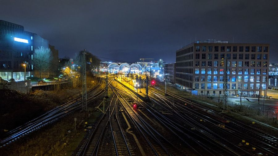 High angle view of illuminated railroad tracks amidst buildings in city