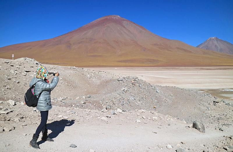 Full length of boy on arid landscape against sky