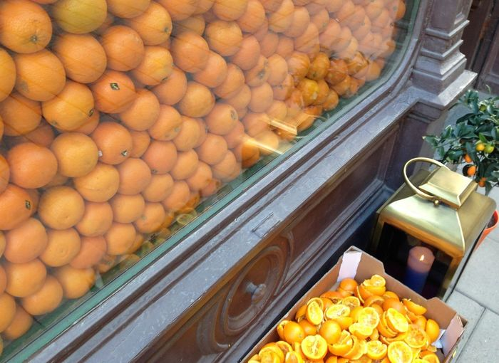 High angle view of oranges at display window by lantern