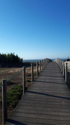 Empty boardwalk against clear blue sky
