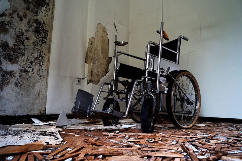 Abandoned wheelchair against broken wall at home