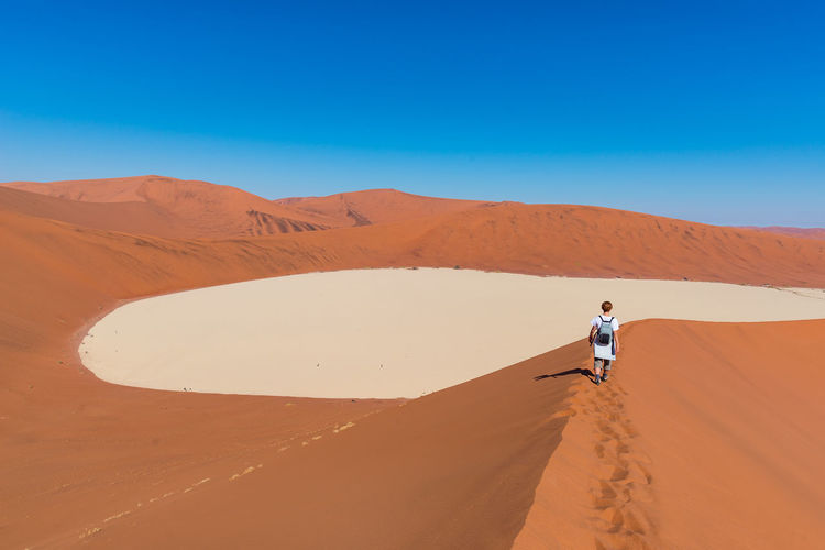 Tourist walking on the scenic dunes of Sossusvlei, Namib desert, Namib Naukluft National Park, Namibia. Adventure and exploration in Africa. Adult Adventure Arid Climate Blue Clear Sky Day Desert Full Length Landscape Nature One Man Only One Person Outdoors People Physical Geography Real People Sand Sand Dune Scenics Sky Standing Young Adult