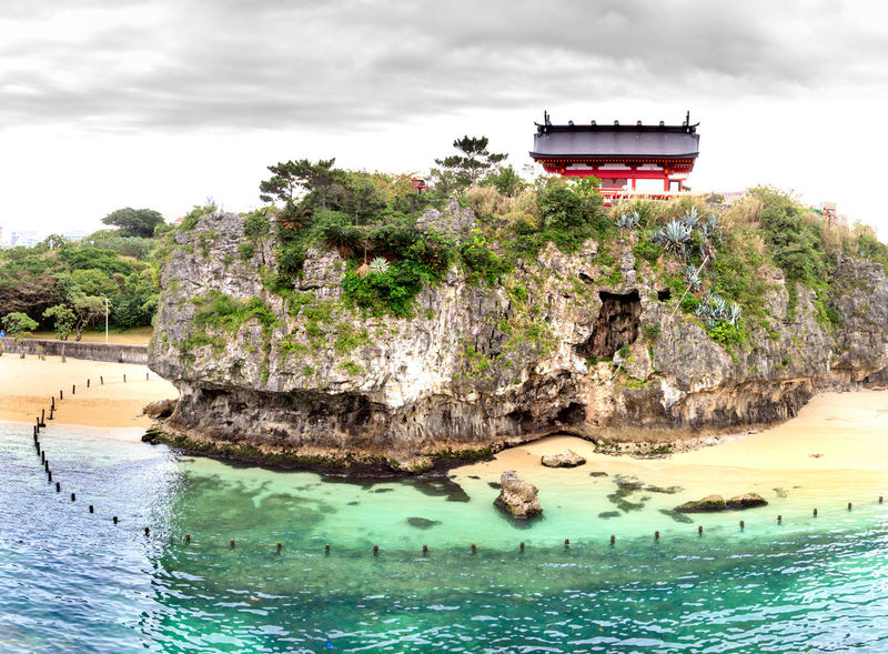 Shinto Shrine on a hill overlooking blue water Shinto Shrine Architecture Beauty In Nature Building Building Exterior Built Structure Cloud - Sky Day Nature No People Outdoors Plant Religion River Rock Rock - Object Sky Tree Water Waterfront