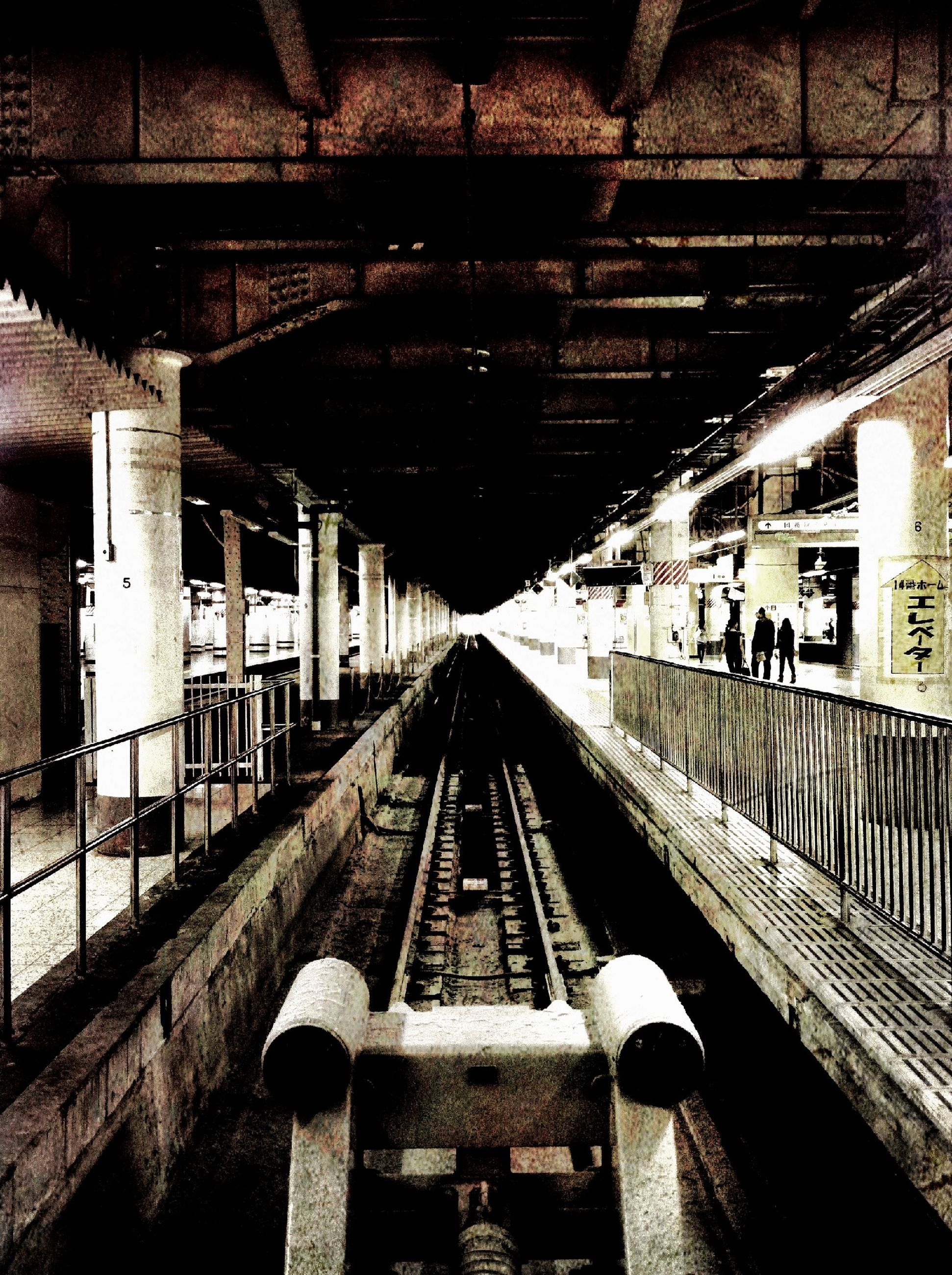 railroad track, rail transportation, railroad station platform, the way forward, architecture, railroad station, diminishing perspective, transportation, built structure, public transportation, indoors, vanishing point, incidental people, railway track, ceiling, travel, tunnel, metal, day