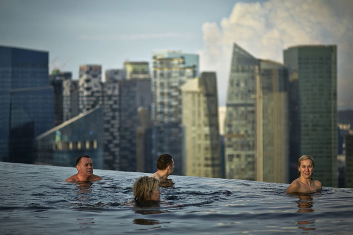 Hotel guests at the Marine Bay Sands infinity pool, overlooking the Singapore skyline City City Cityscape Destination Focus On Foreground Headshot Infinity Pool Leisure Activity Lifestyles Outdoors Person Singapore Skyline Skyscraper Swimming Travel Water