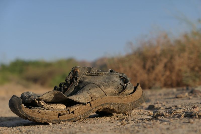 Close-up of abandoned shoes on field against sky