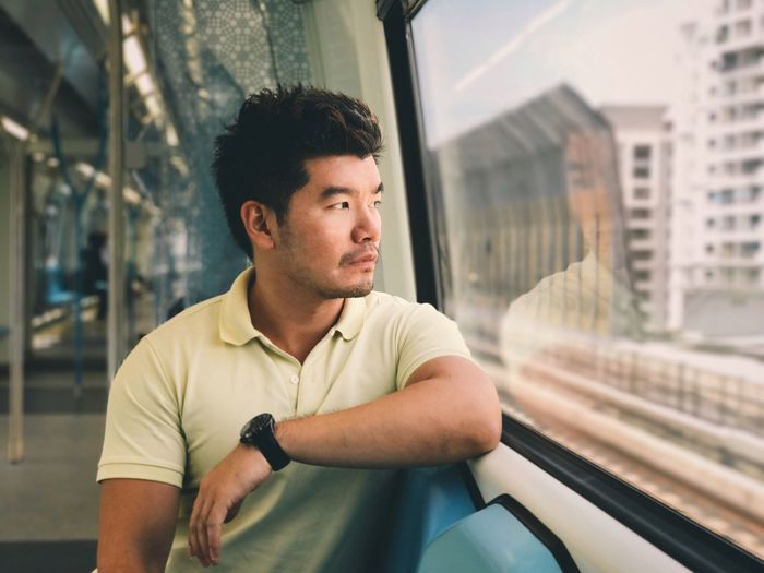 Looking out Transportation One Person Real People Mode Of Transport Public Transportation Window Casual Clothing Train - Vehicle Travel Lifestyles Journey Wristwatch Young Adult Young Men Day Technology Urban City Indoors  Asian  Train Indoor EyeMeNewHere Reflection