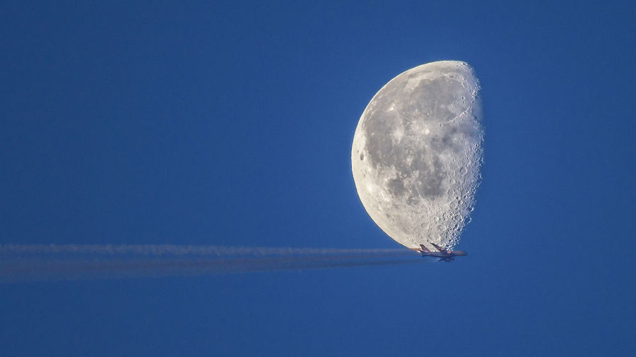 Low angle view of airplane against half moon