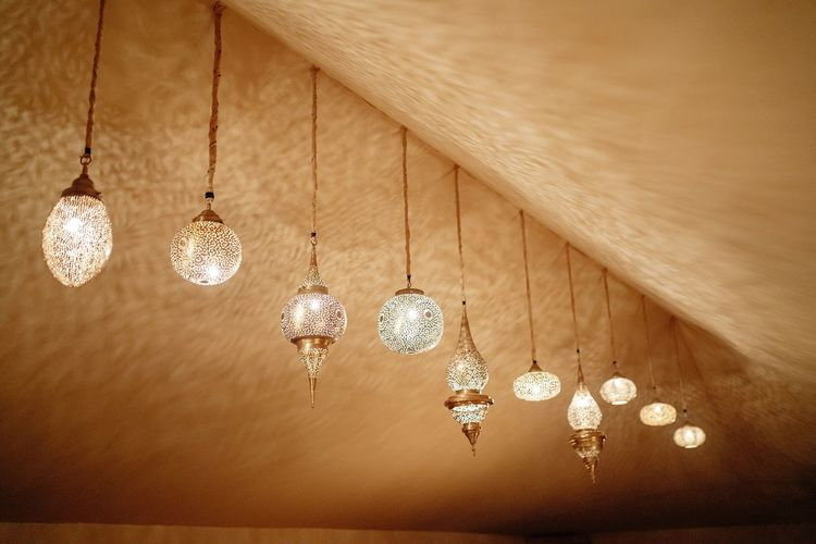Directly below shot of illuminated pendant lights hanging on ceiling