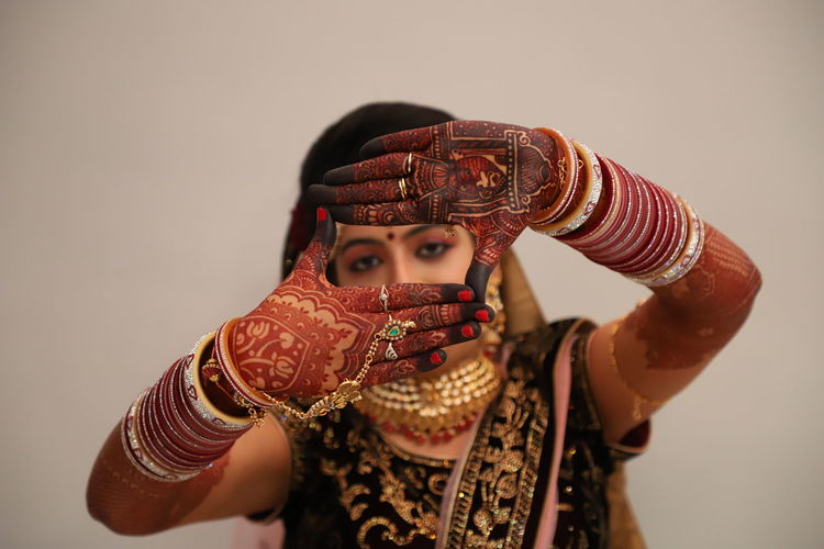 Close-up portrait of bride gesturing against beige background
