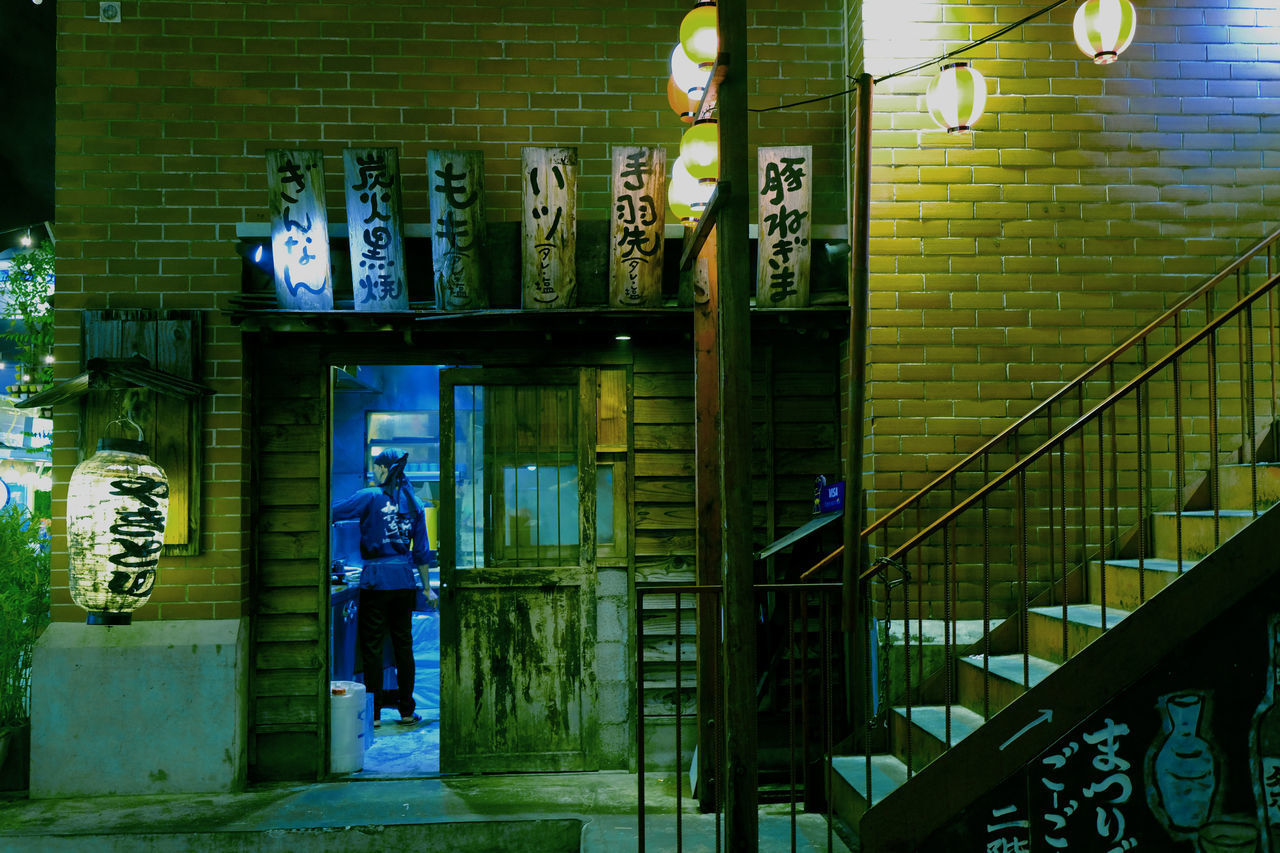 REAR VIEW OF MAN STANDING IN ILLUMINATED BUILDING