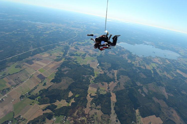 People skydiving over landscape