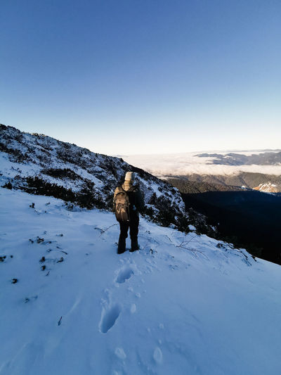 Rear view of person standing on snowcapped mountain against sky