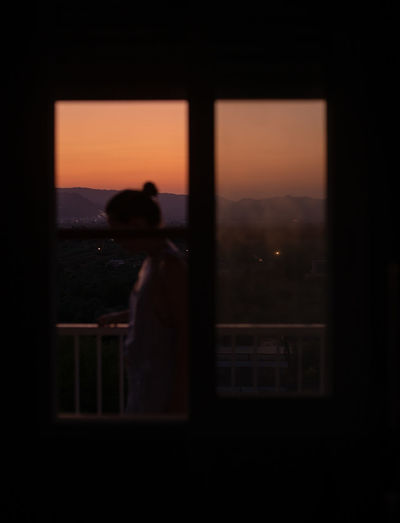 Silhouette woman standing by window against orange sky