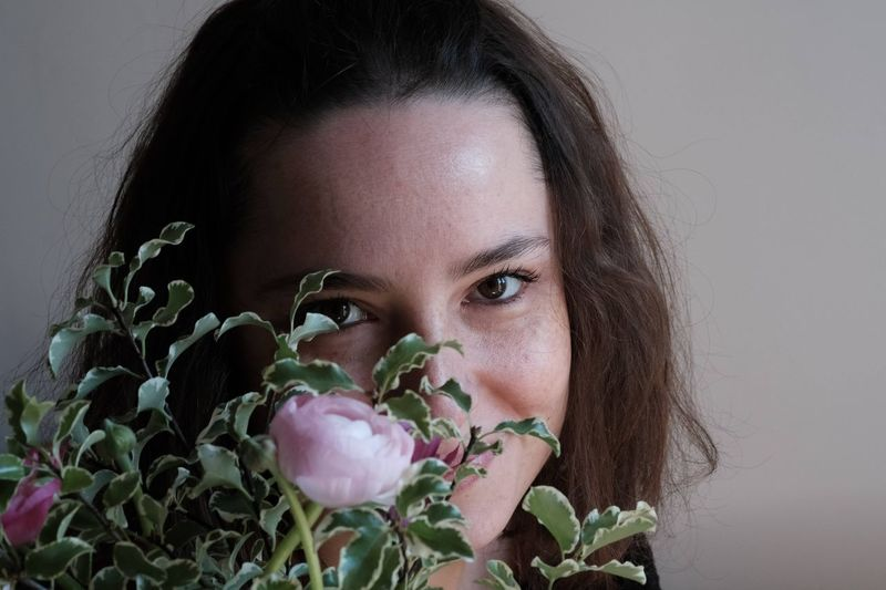 Close-up portrait of woman with pink flower