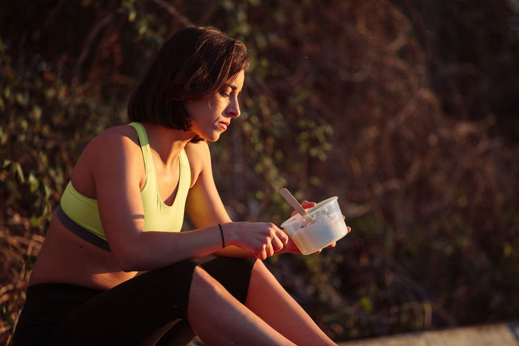 Young woman eating food while sitting at park