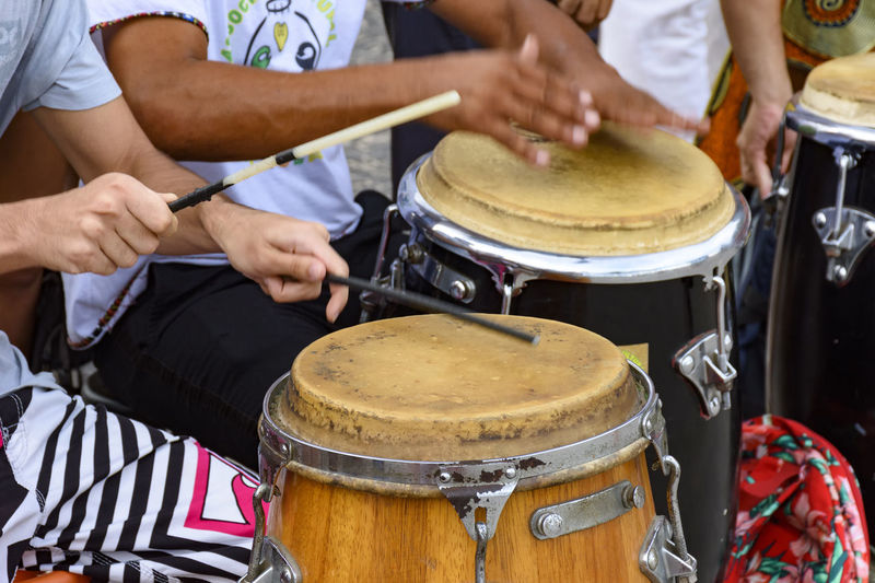 Midsection Of People Playing Drum