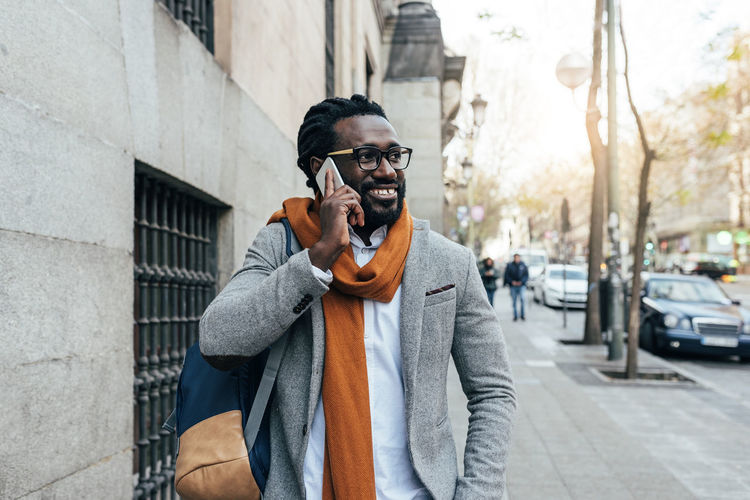 Businessman talking on phone while walking on sidewalk in city