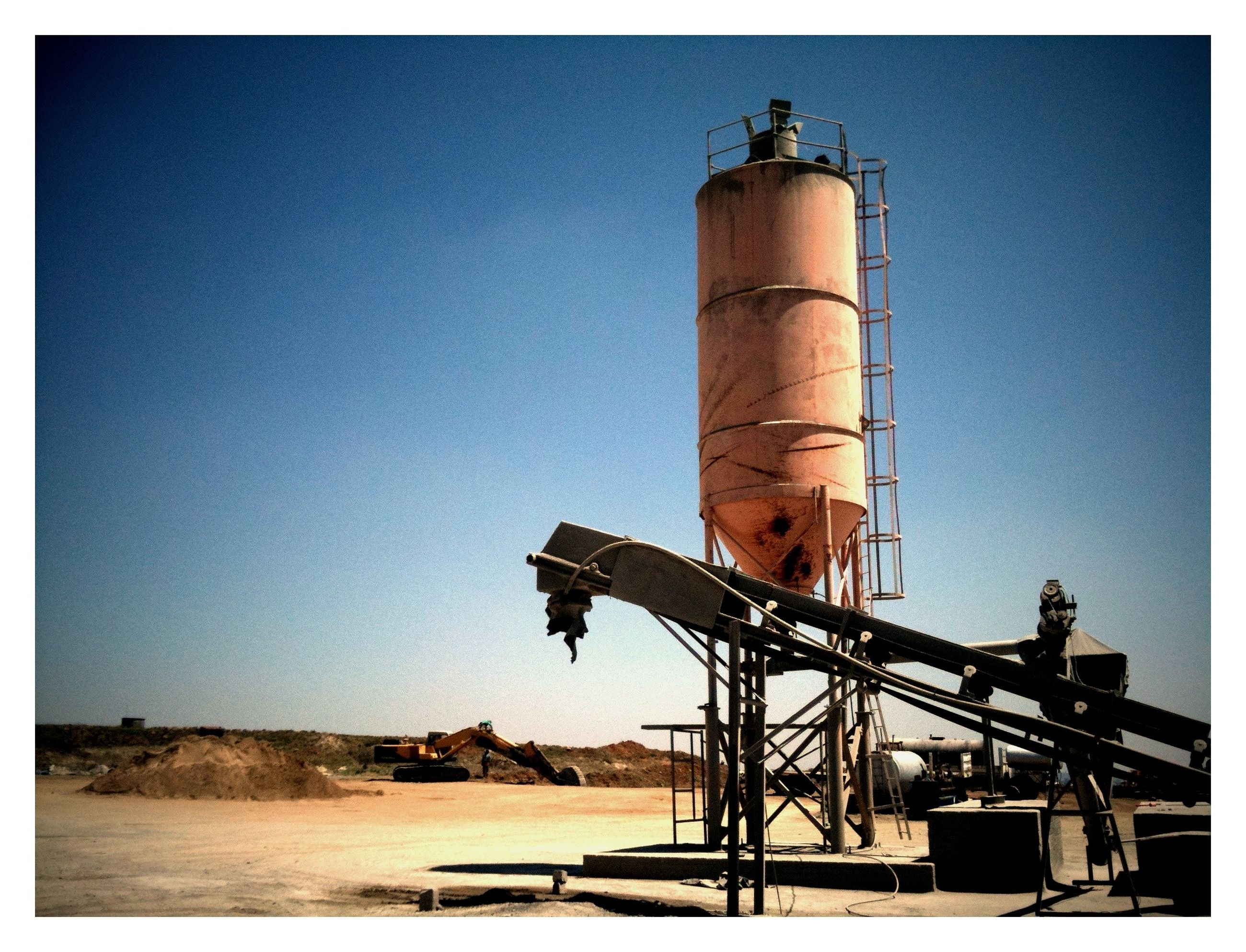 clear sky, transfer print, built structure, auto post production filter, architecture, copy space, industry, building exterior, lighthouse, sky, fuel and power generation, environmental conservation, low angle view, day, outdoors, construction site, no people, sand, wind power, guidance