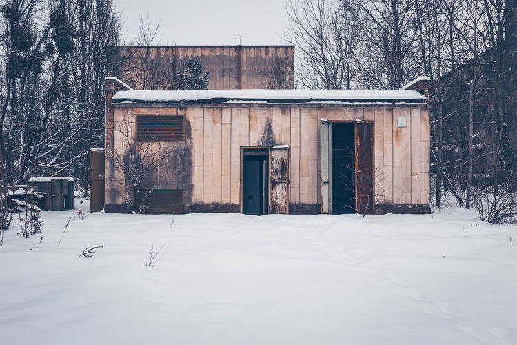 House and bare trees by building during winter