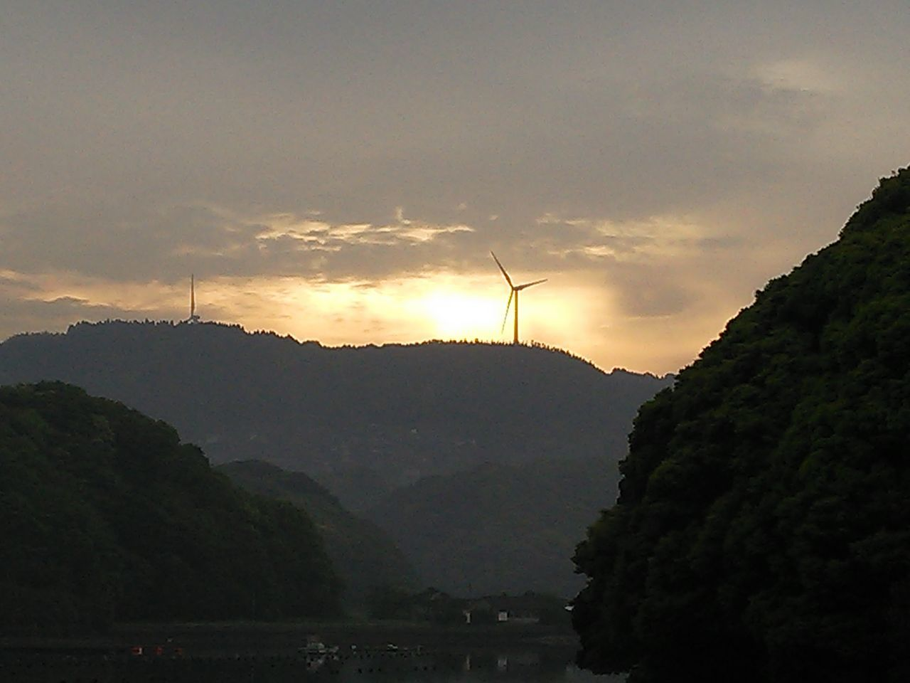 environmental conservation, beauty in nature, fuel and power generation, tree, nature, sky, alternative energy, sunset, renewable energy, mountain, silhouette, outdoors, scenics, cloud - sky, no people, sun, tranquil scene, tranquility, wind power, windmill, wind turbine, low angle view, day, industrial windmill