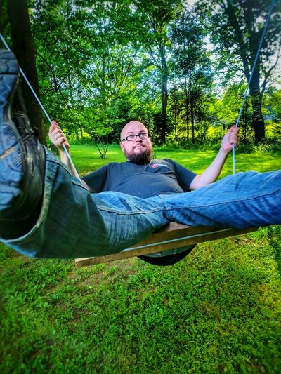 Man sitting on swing over field