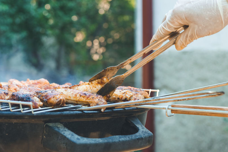 Cropped hand of chef preparing barbecue