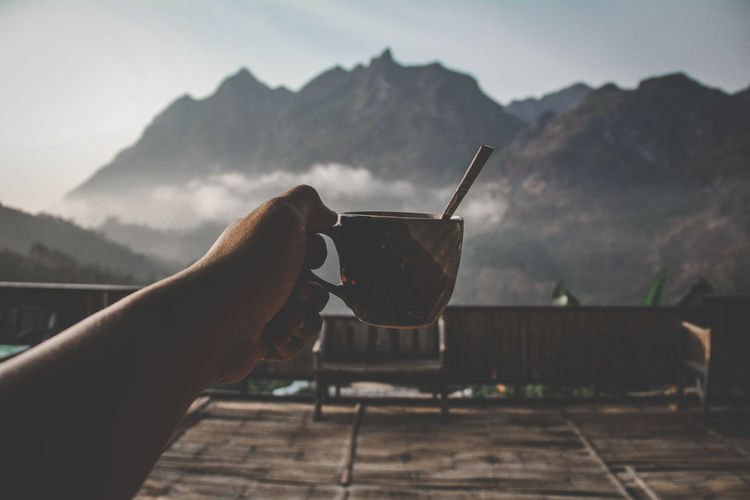 Cropped image of hand holding drink against mountain range