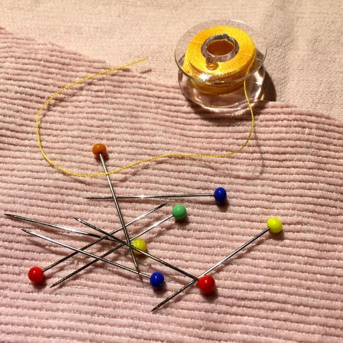 Close-Up Of Thumbtacks And Thread Spool On Fabric