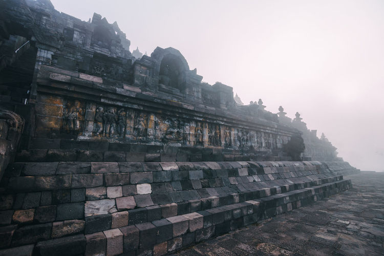 Blanket of morning fog slowly engulfs the first gallery of Borobudur Temple. A must see in Yogyakarta, Indonesia, Stone Wall Ancient Civilization Building Day Ancient Spirituality Belief The Past Religion Tourism History Travel Building Exterior Place Of Worship Built Structure Architecture Foggy Morning Wonderful Indonesia Famous Place A Must See Backpacker Vacations Travel Destinations Borobudur Buddhism Buddhist Temple Carvings Buddha UNESCO World Heritage Site Yogyakarta My Best Photo 17.62°